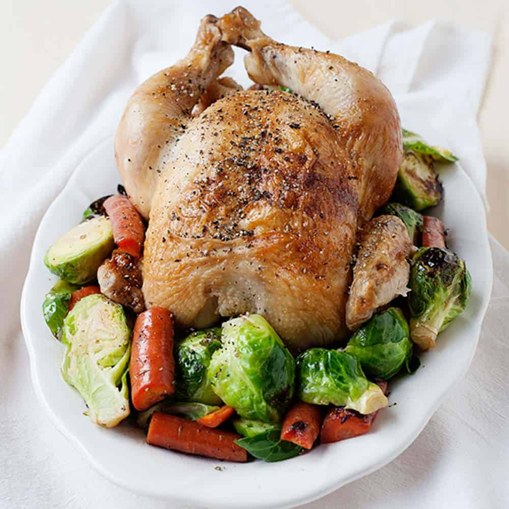 image: baked whole chicken on a platter on top of roasted vegetables