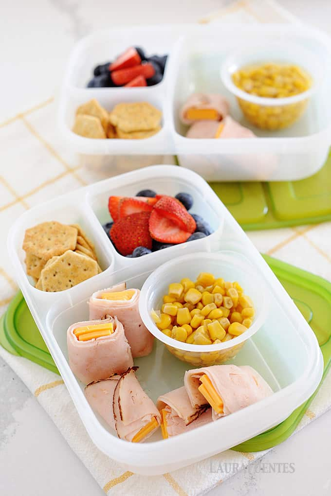 image: two lunch containers filled with crackers, fruit, ham roll ups and corn