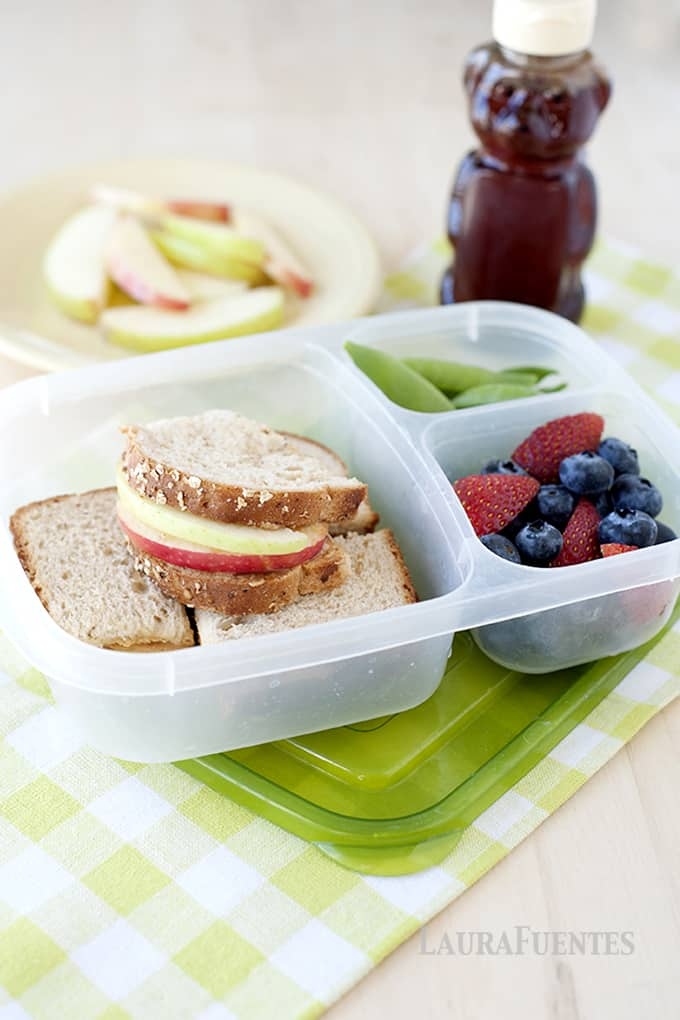 image: lunch container with apple sandwiches, snap peas and fruit
