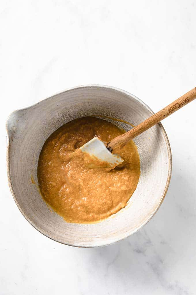 step by step recipe image: Step 4 - wet cookie ingredients being mixed in a bowl. Including pumpkin puree, egg, butter and sweeteners.