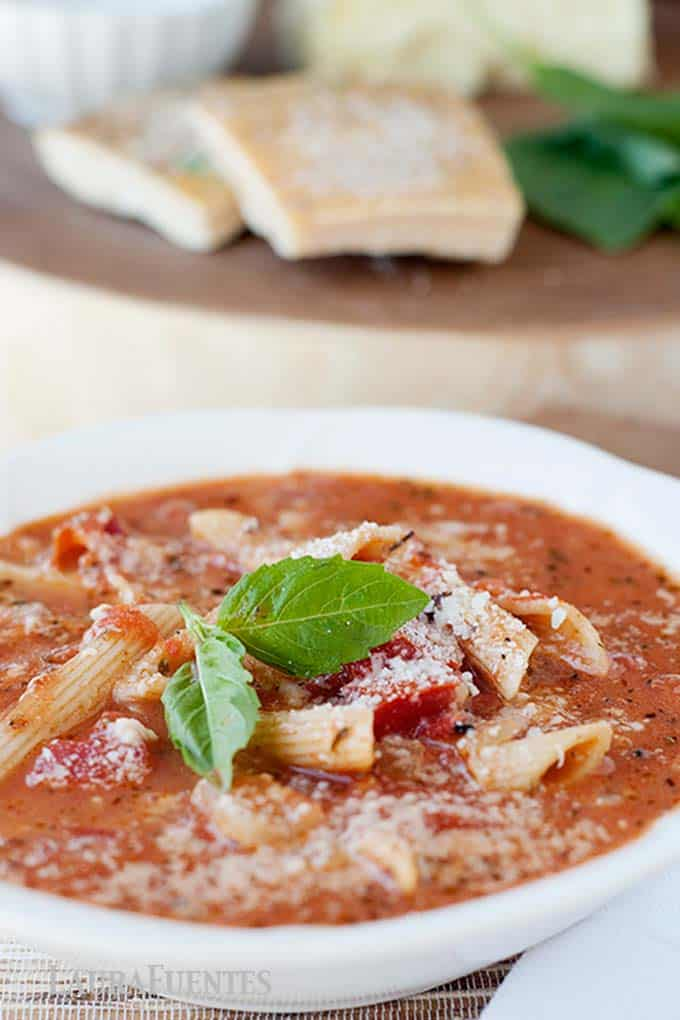 image: bowl of chicken and pasta soup, with blocks of parmesan cheese in the background.