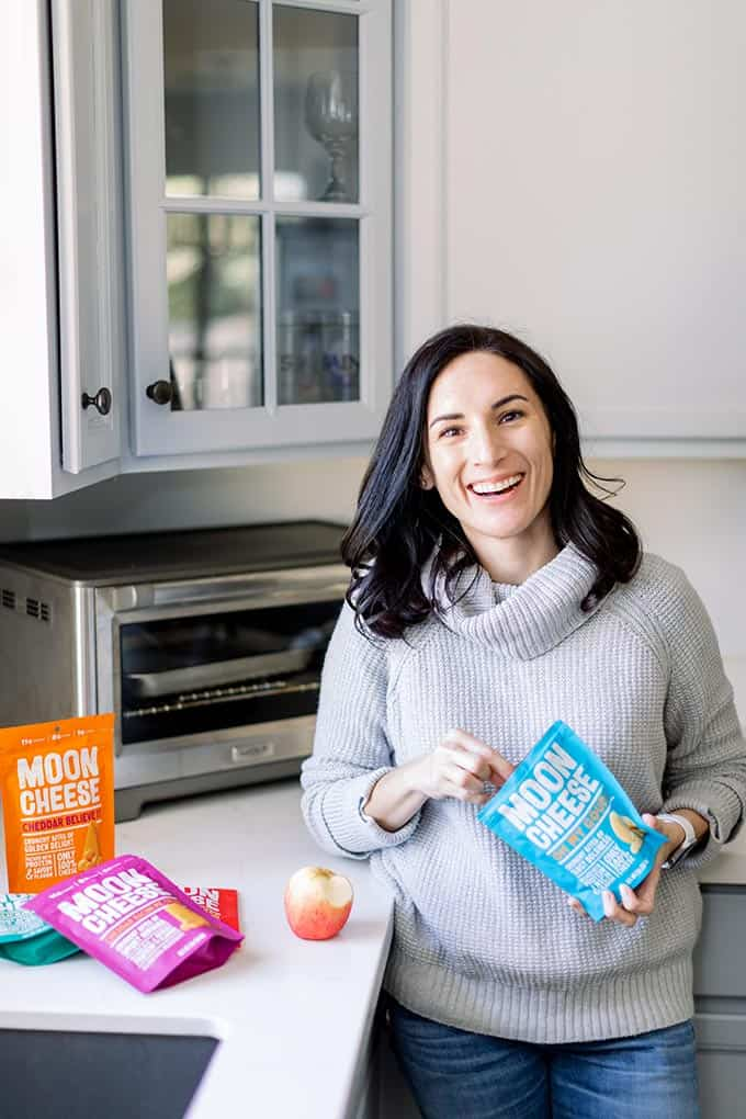 image: woman standing in kitchen with apple and bags of Moon Cheese snacks