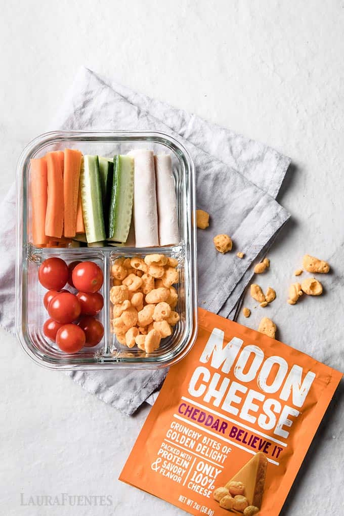 image: glass container with rolled up turkey slices, sliced carrots and cucumber, grape tomatoes and moon cheese snack