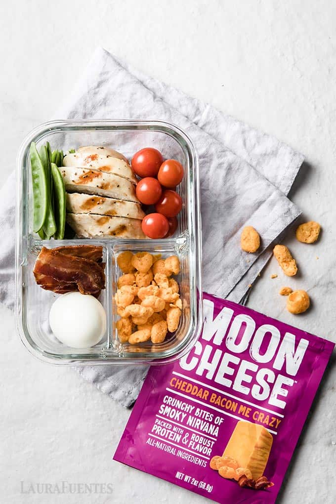 image: glass snack container with moon cheese snacks, slices of bacon, hard-boiled egg, grilled chicken breast and vegetables.