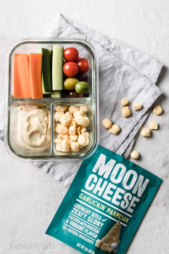 image: glass snack container with tomatoes, olives, carrot sticks, cucumber sticks, hummus and moon cheese snacks.