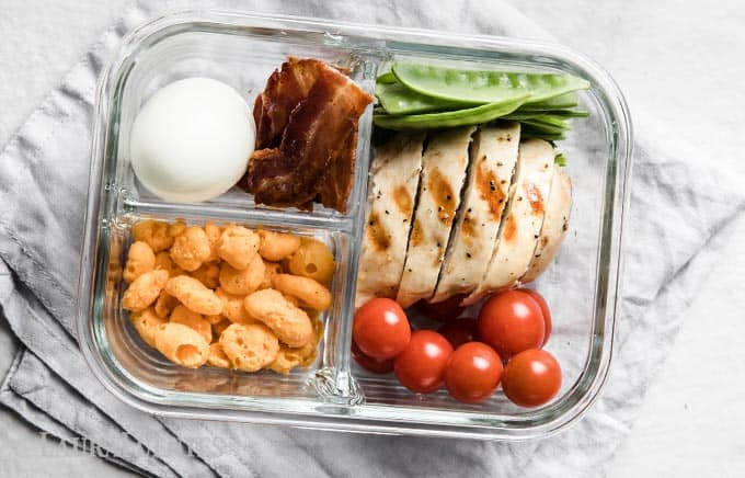 image: glass snack container with chicken slices, grape tomatoes, snow peas, bacon, hard boiled egg and cheese bites.