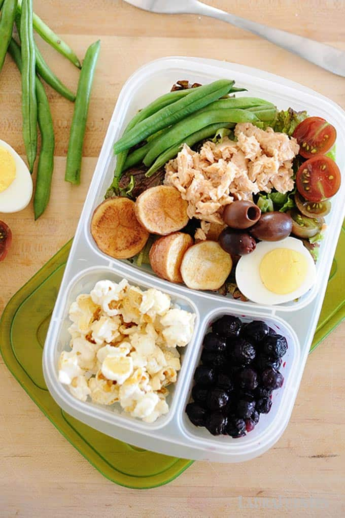 image: lunch container with salmon salad, popcorn and fruit