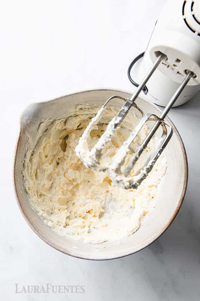 Step by step recipe images: step 5 white frosting being blended in a bowl with a hand mixer