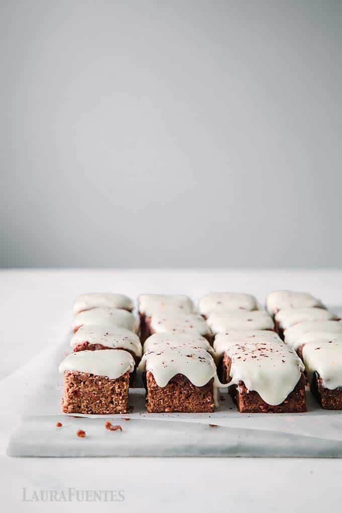 image: tray of chocolate brownies in rows with white frosting
