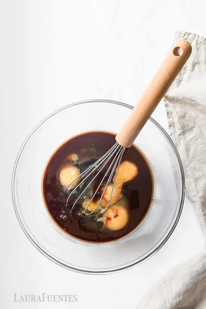 Recipe step by step images step 2:  bowl of melted chocolate with eggs and whisk