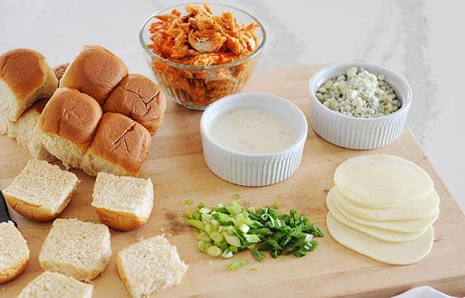 image: ingredients for buffalo chicken sliders laid out on a cutting board. Including, bowl of buffalo chicken, blue cheese crumbles, provolone cheese slices, dish of ranch dressing, chopped green onions and small rolls.