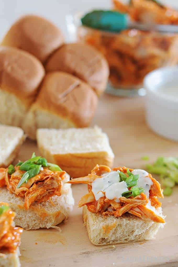 image: process-photo making buffalo chicken sliders. Drizzling ranch dressing over the chicken.
