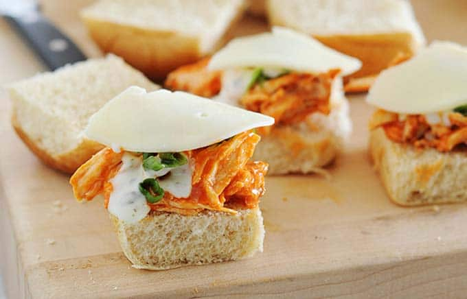 image: In-process photo making buffalo chicken sliders. Stacking cheese slices over buffalo chicken, sauce and green onions.