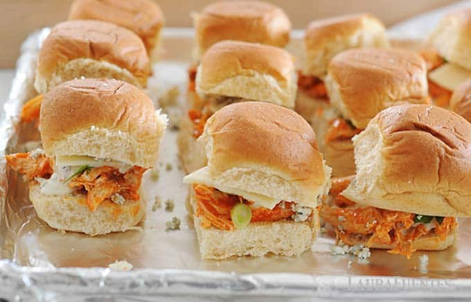 image: Buffalo chicken sliders assembled and placed in rowson a baking sheet.