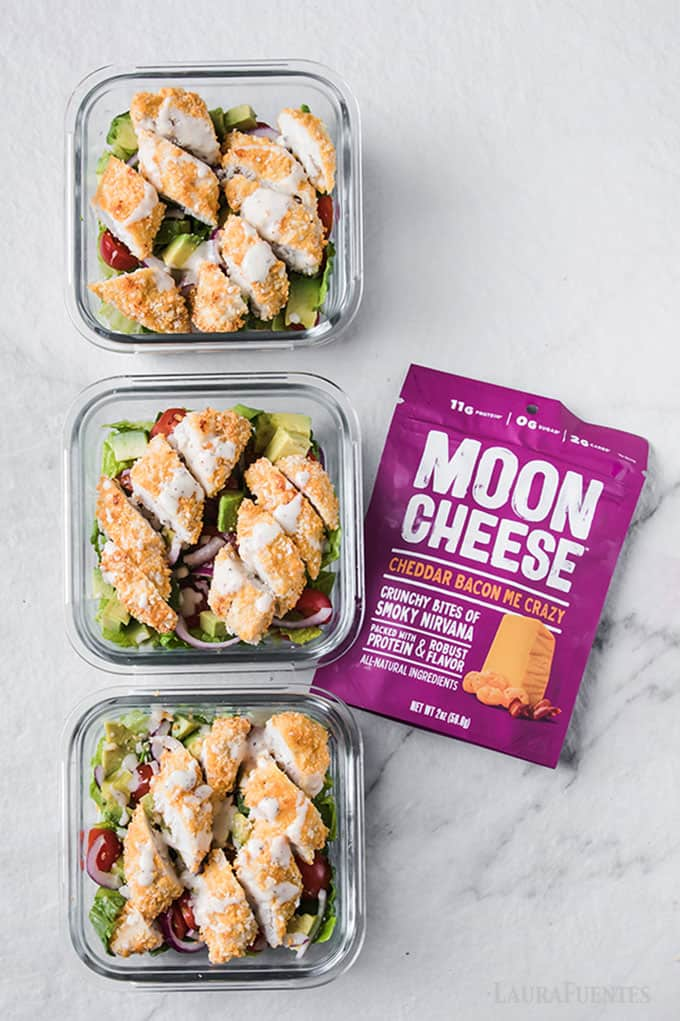 image: three salads topped with chicken in square meal prep dishes. One purple bag of moon cheese snacks next to the three salads