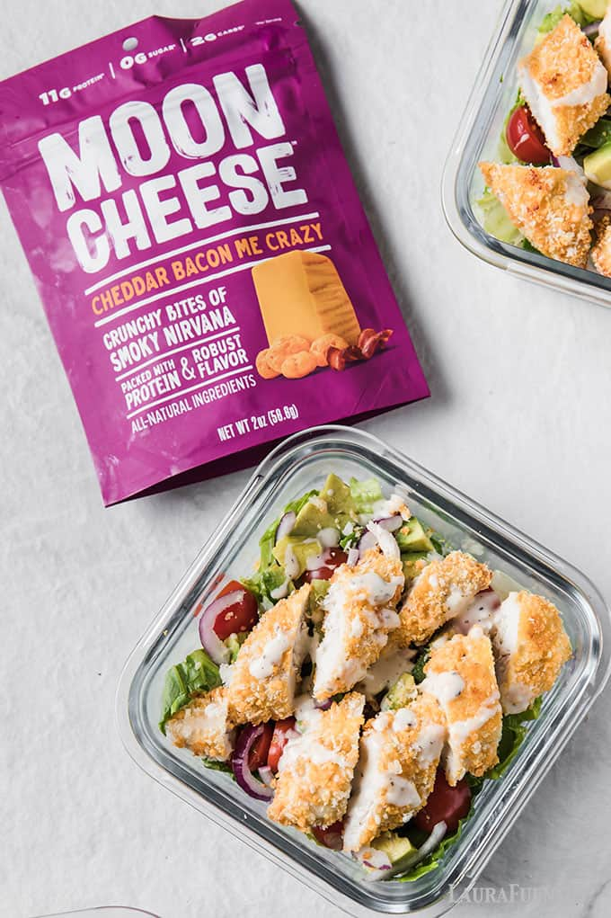 image: purple bag of cheddar moon cheese snacks next to square glass salad dish with meal prepped salad