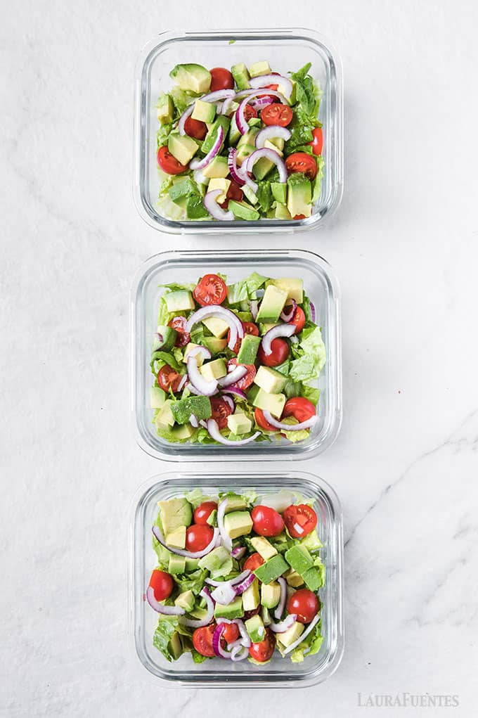 image: three square glass meal prep dishes filled with lettuce, tomatoes, avocados and onion slices.