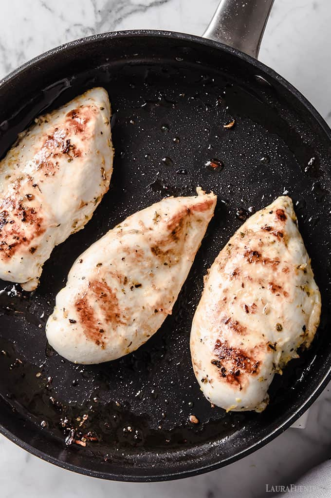 image: three chicken breasts cooking in a pan