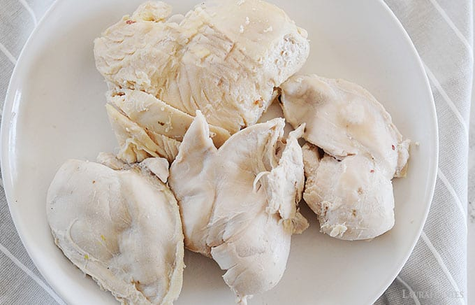 image: freshly poached chicken breasts on a plate
