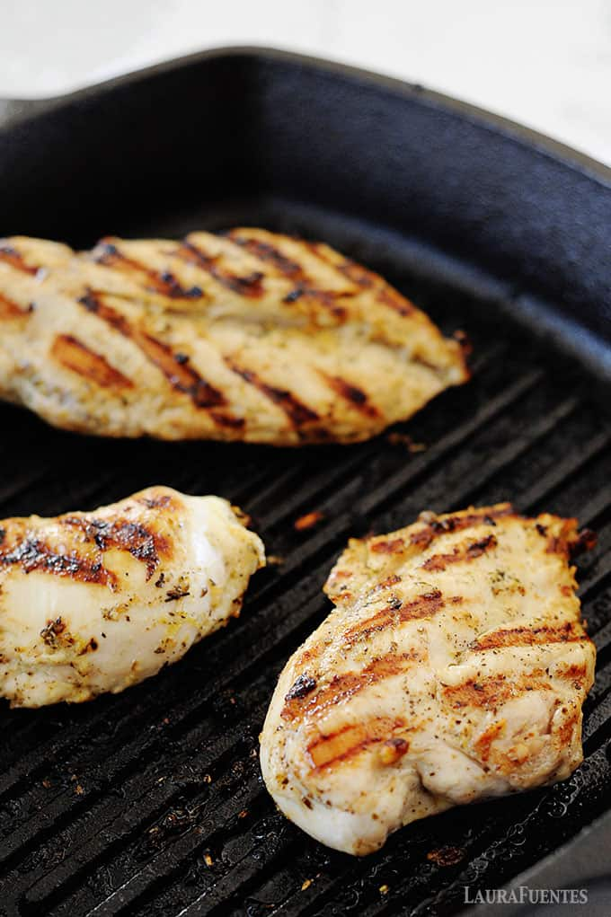 image: three cooked chicken breasts on an indoor grill pan