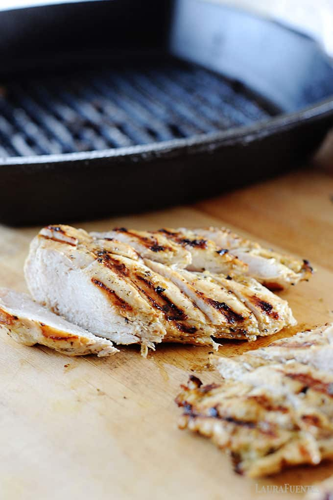 image: chicken breast being sliced on a cutting board next to indoor grill pan