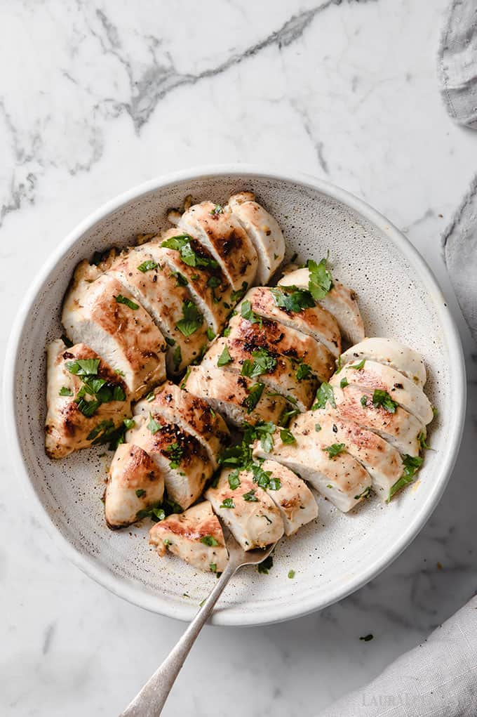 image: three sliced chicken breasts with spices in a shallow white bowl with a fork