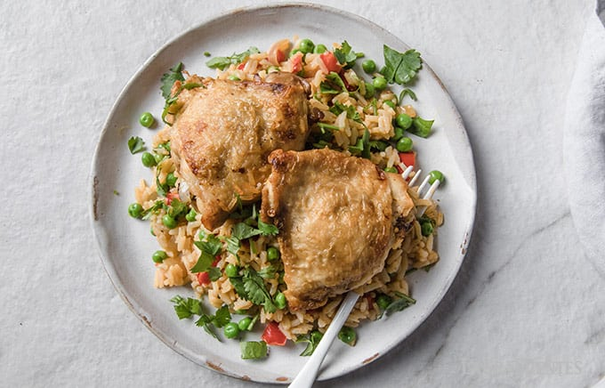 image: two chicken thighs on a plate with rice and vegetables