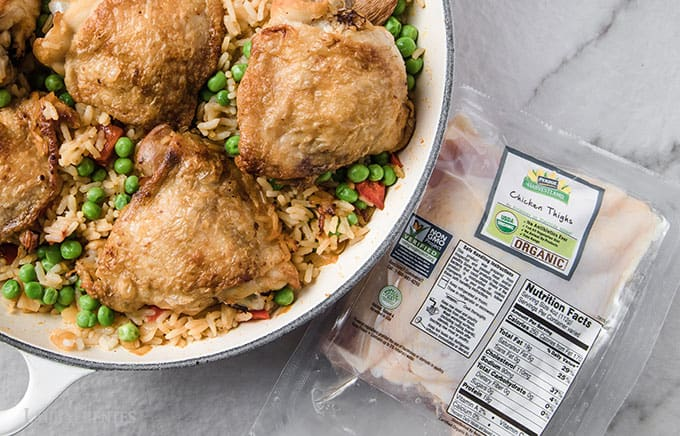 image: skillet full of Spanish chicken and rice next to package of Perdue organic chicken thighs
