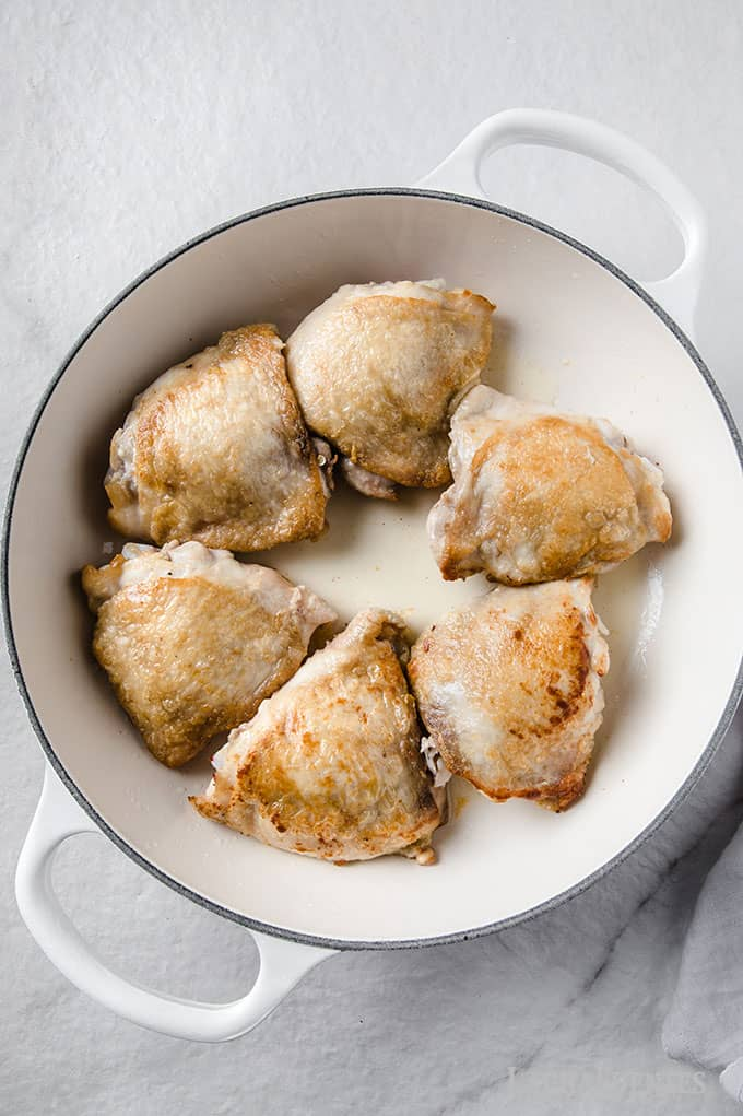 Image: Process shots making Spanish chicken - chicken thighs browned in a skillet