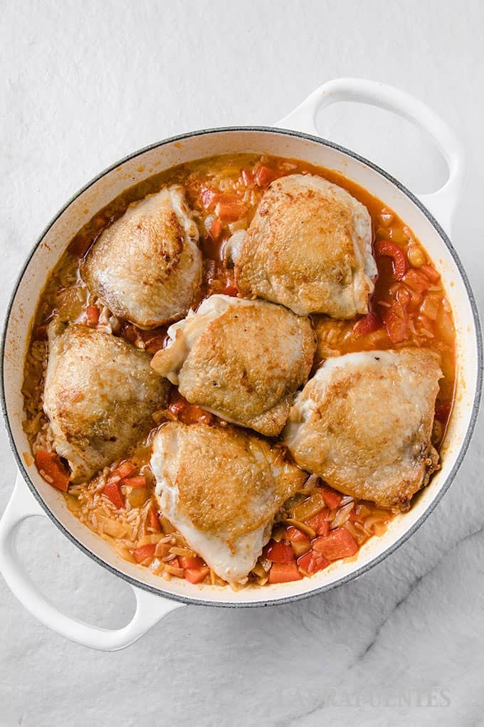 image: step four cooking Spanish add chicken thighs to skillet with rice and vegetables