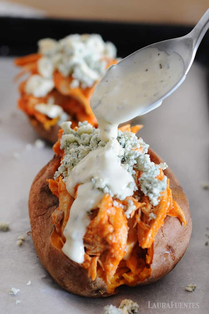 image: two baked sweet potatoes with buffalo chicken and blue cheese crumbles. A spoon of ranch dressing pouring over the top of one potato