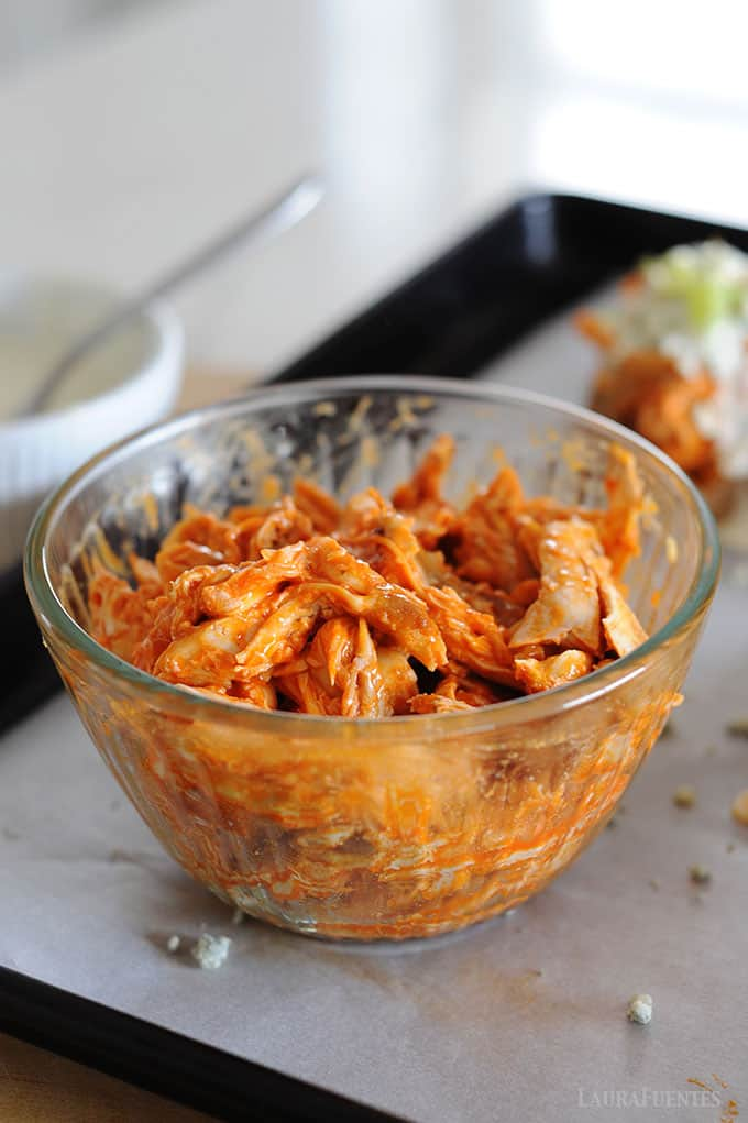 image: large glass bowl of shredded chicken with buffalo sauce