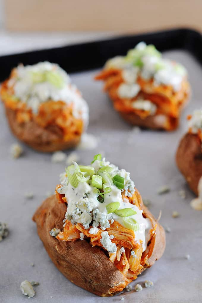 image: four baked sweet potatoes on cooking sheet loaded with buffalo chicken, ranch dressing, green onions and blue cheese crumbles