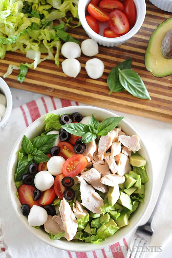 image: Large bowl of chicken salad with tomatoes, olive slices, halved cherry tomatoes, mozzarella balls and diced avocado.