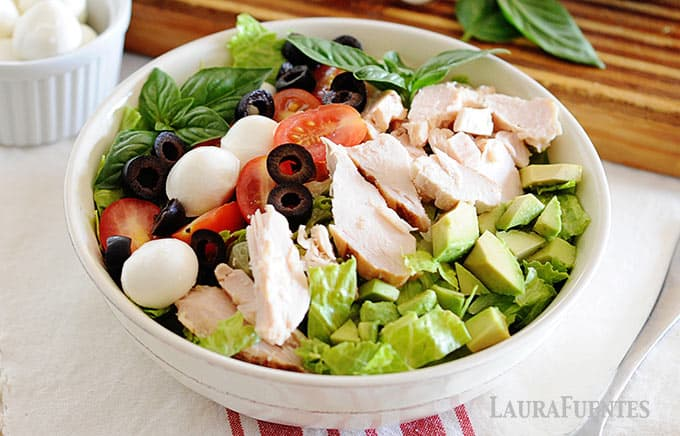 image: large bowl of chicken salad with tomatoes, olives, avocados, cheese and lettuce
