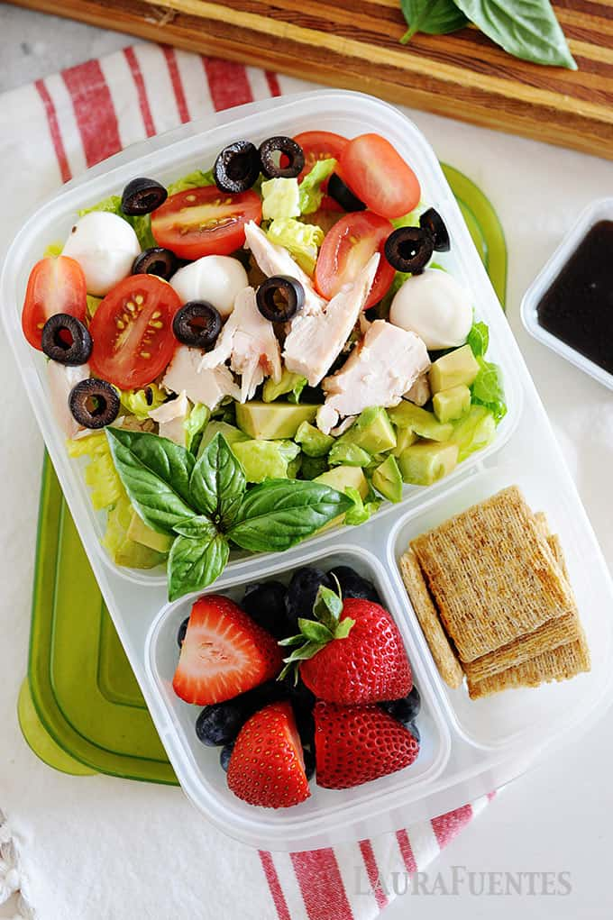 image: chicken caprese sald in a lunch container with berries and crackers
