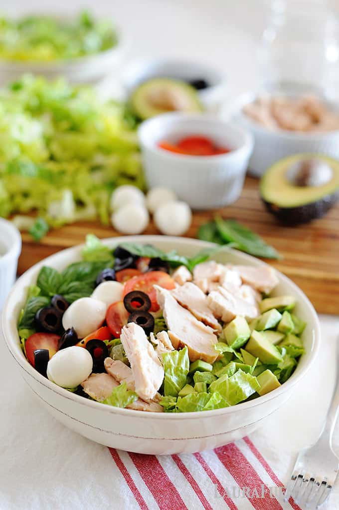 image: Large white bowl of salad with avocado, olives, cheese balls, tomatoes and chicken