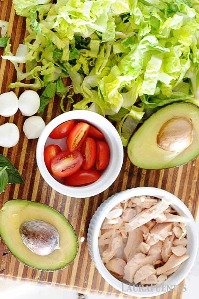 image: ingredients for chicken caprese salad, lettuce, avocados, chicken, cheese and tomatoes