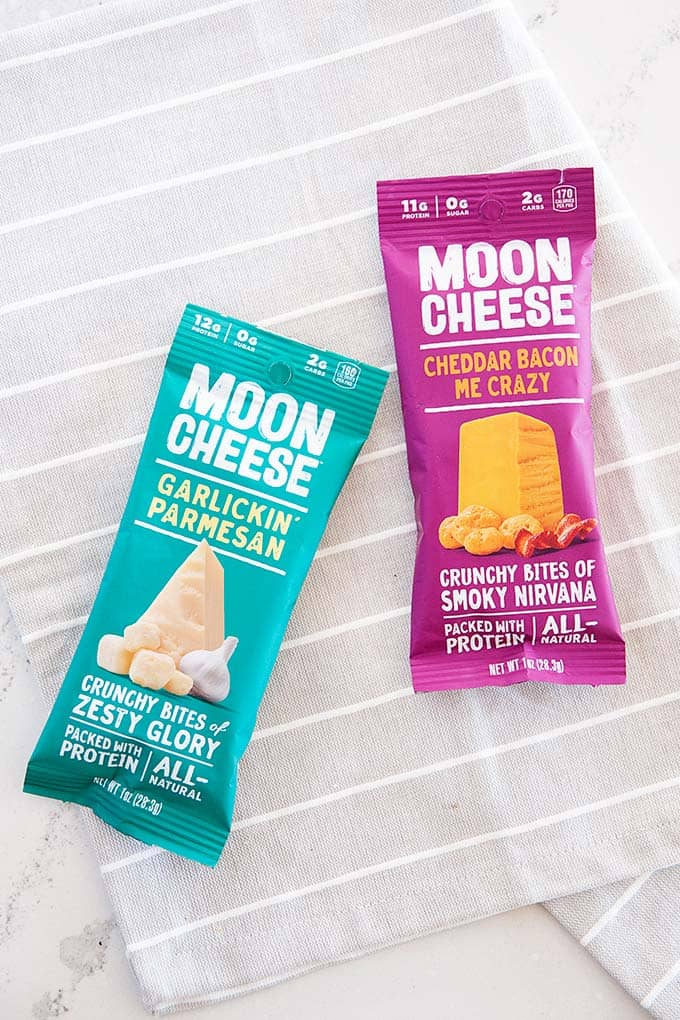 image: two small bags of moon cheese snacks on a grey cloth