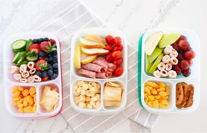 image: overhead view of three snack boxes side by side filled with high protein snack options.