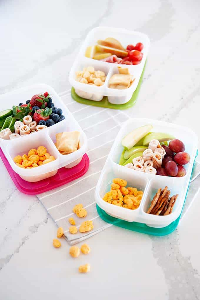 image: three lunchbox containers  filled with high protein snacks like berries, moon cheese, lunch meat and fruit.