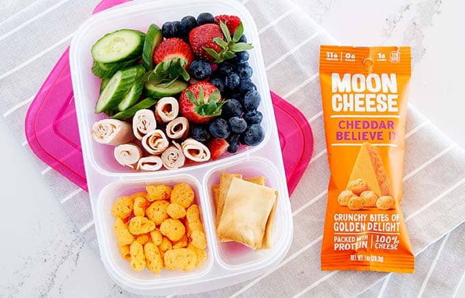 image: overhead shot of snack box filled with pita chips, berries, cucumber slices, turkey rolls and moon cheese snacks. Orange bag of moon cheese snacks next to snack box.