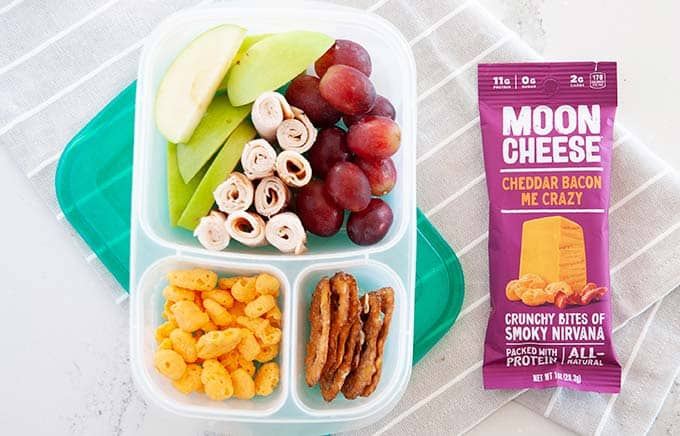 image: overhead shot of snack box filled with pretzels, grapes, green apple slices, turkey rolls and moon cheese snacks. Purple bag of moon cheese snacks next to snack box.