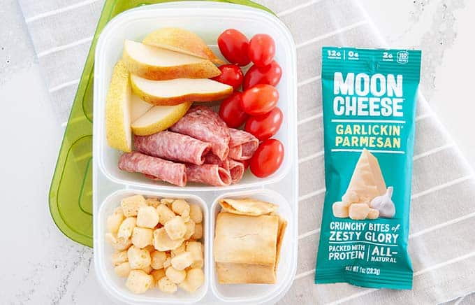 image: overhead shot of snack box filled with pita chips, grape tomatoes, red apple slices, rolled salami slices and moon cheese snacks. Green bag of moon cheese snacks next to snack box.