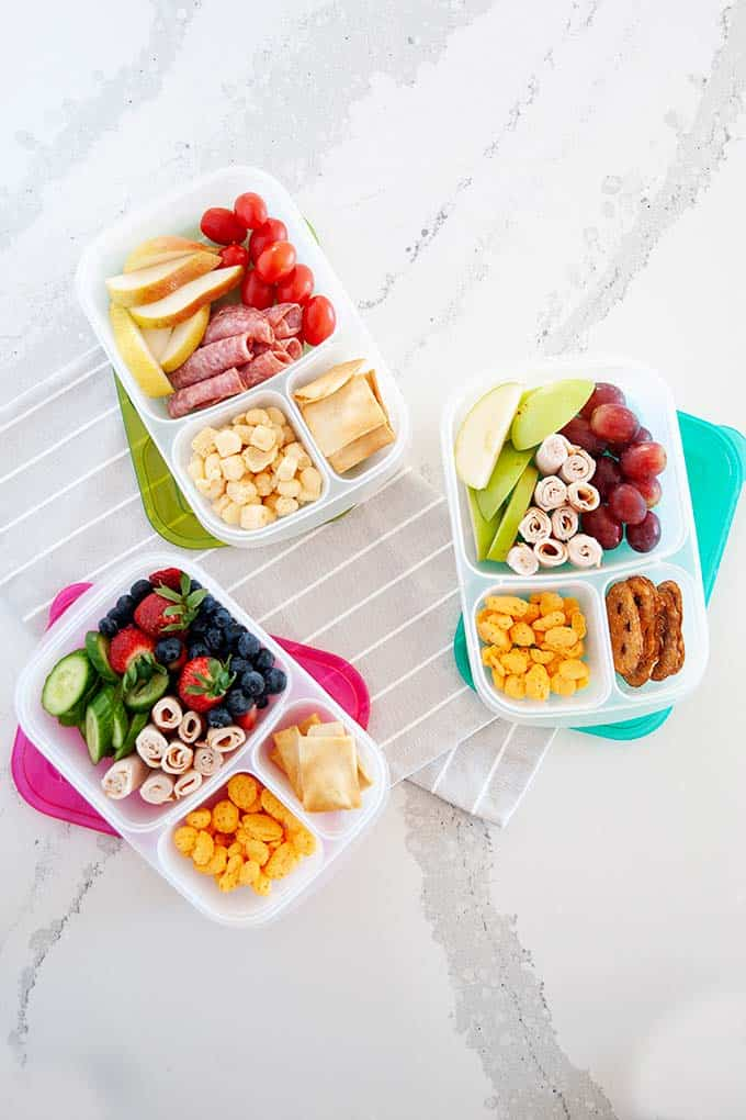 image: overhead view of three lunchbox containers  filled with high protein snacks like berries, moon cheese, lunch meat and fruit.