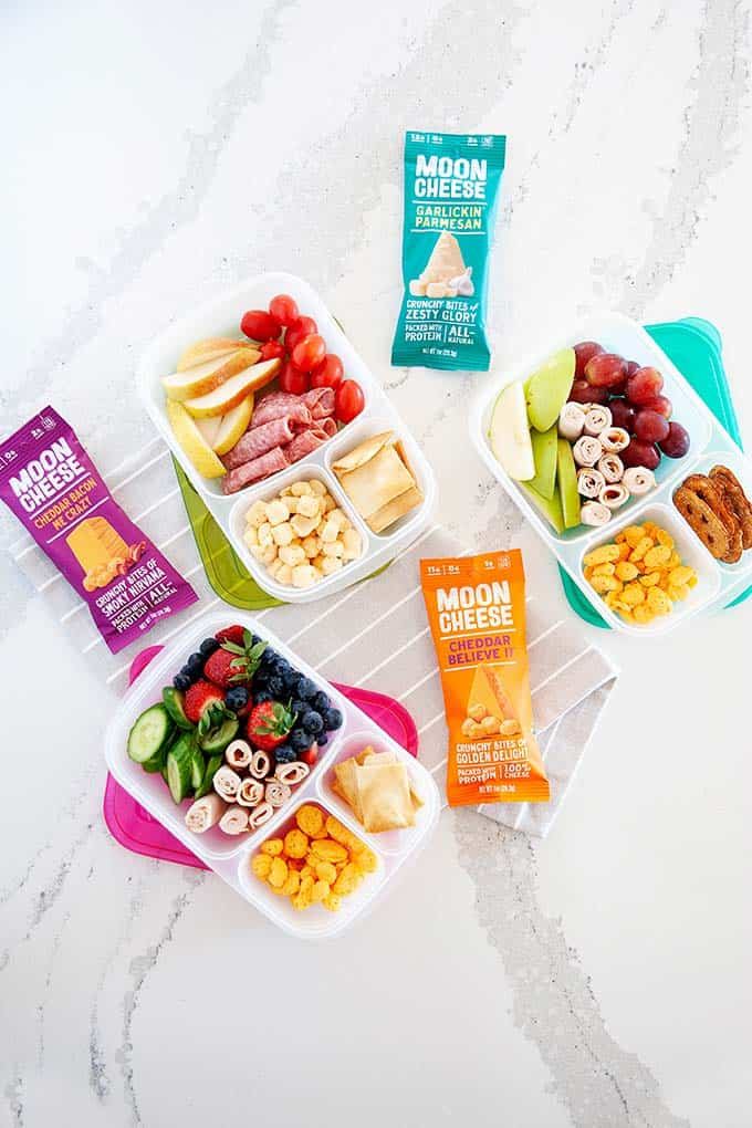 image: overhead view of three lunchbox containers  filled with high protein snacks like berries, moon cheese, lunch meat and fruit. Three snack size bags of moon cheese next to the snack boxes.