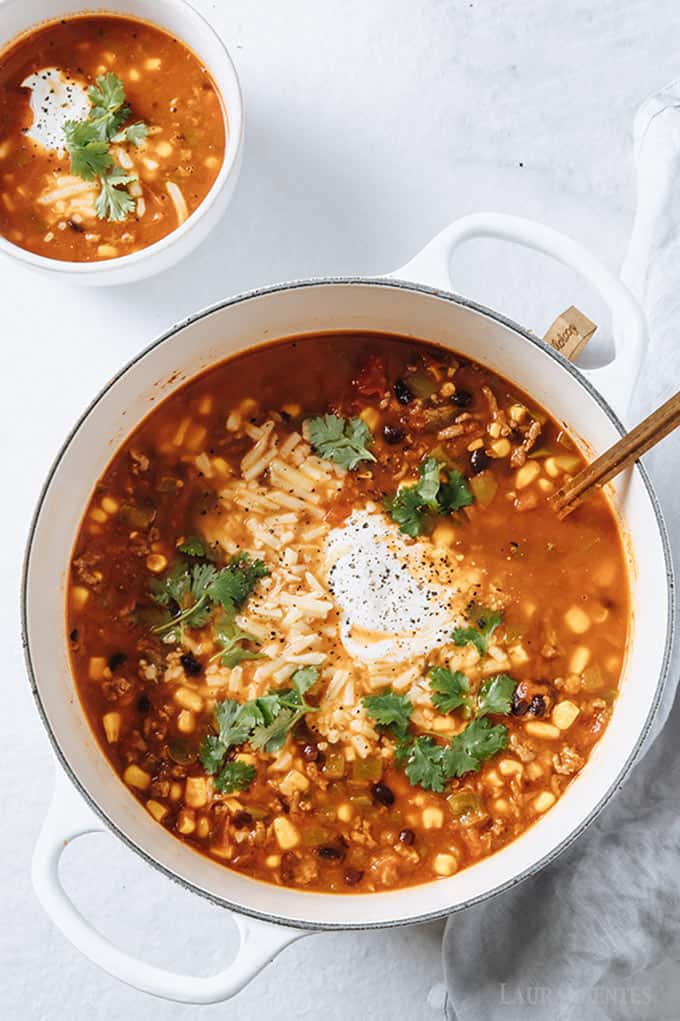 image: large bowl of taco soup topped with sour cream, with large ladle in the pot.