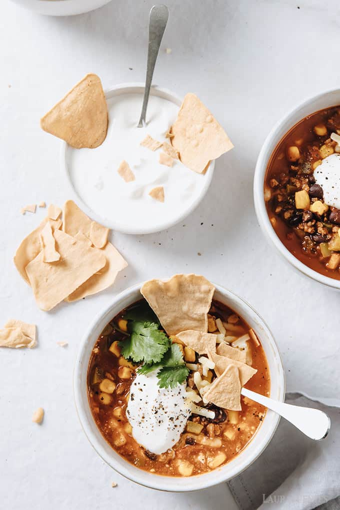 image: two small bowls of taco soup, topped with shredded cheese, cilantro, and tortilla chip pieces. Another small bowl of sour cream sits to the side with chip pieces inside.