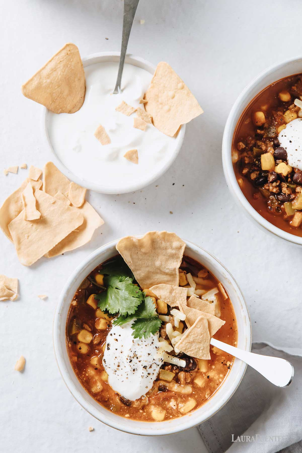 two bowls of taco soup topped with chips.
