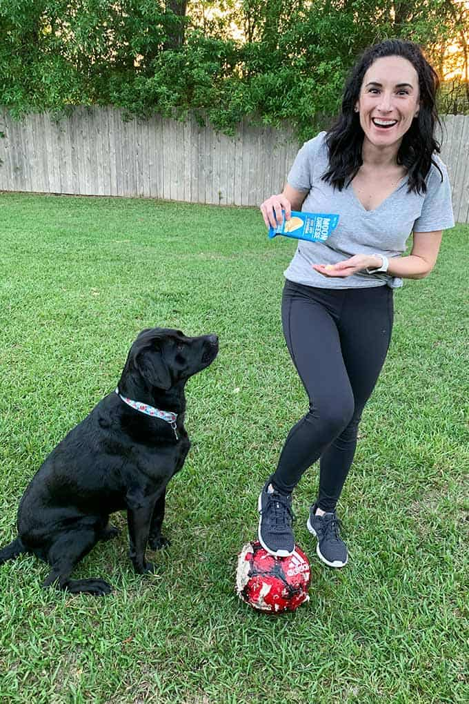 image: woman in backyard with dog, and small bag of moon cheese snacks
